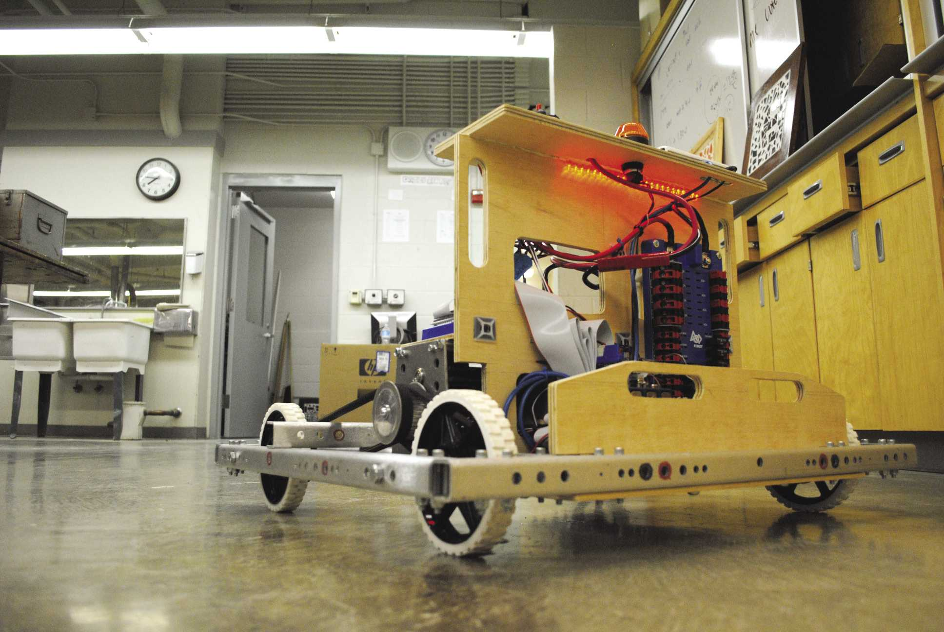 The 37-pound unfinished robot (right) is estimated to be 110 pounds upon completion. The fully functional robot is powered by two 80-amp motors, operated with a joystick and equipped with an emergency shutoff switch.  Photos by Nic Olson