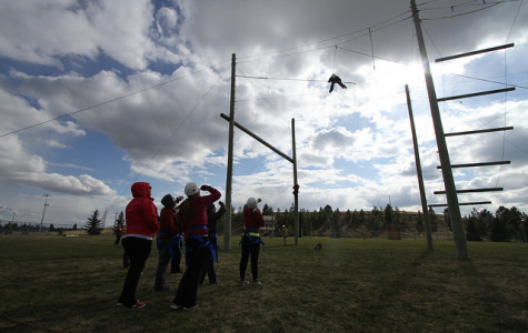 Students look up at the challenge of balaning on the thin wire as the wind is howling. The Challenges range from 25-40 feet in the air.