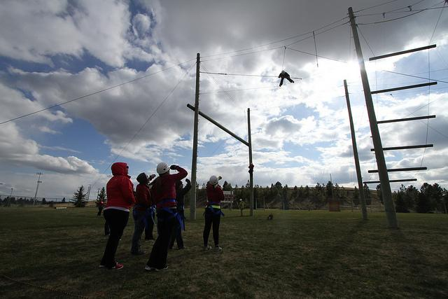 Students+look+up+at+the+challenge+of+balaning+on+the+thin+wire+as+the+wind+is+howling.+The+Challenges+range+from+25-40+feet+in+the+air.
