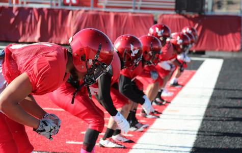 Photo by: Josh Friesen  Cornerbacks and safeties prepare in athletic stances to begin a drill during practice.