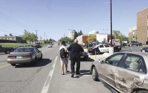 Saleh Alsudais is consoled by a Cheney Police officer after Alsudais discovered that his car was involved in a collision outside Cadet Hall. His car was one of five cars damaged May 9.