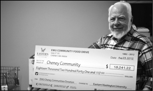 Photo by Sam Sargeant  John Matthews poses with a check donated to the Cheney food bank.