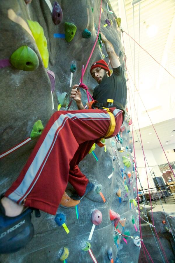 Photo by Sam Sargeant Yasser Mohammad tests for a foot hold, as he scales the rock climbing wall at the URC.