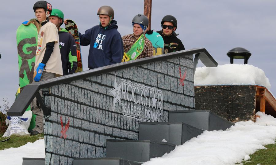 Snowboarders watch another participant as they wait in line at the rail jam to shred powder on Oct. 5.