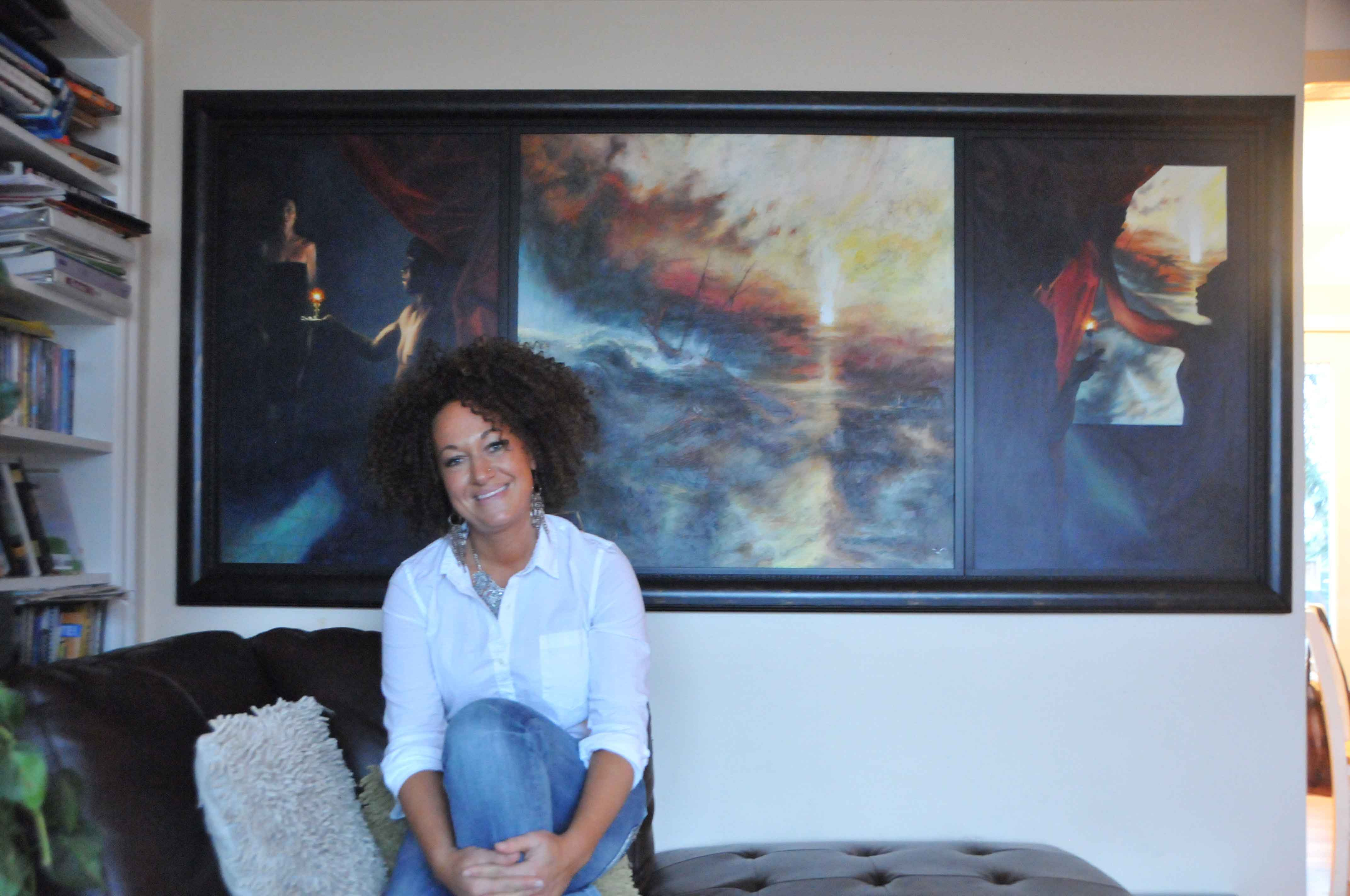 Rachel Dolezal, an EWU Professor, sits on a couch at her home in front of an original painting she created. Dolezal obtained her master's in fine arts at Howard University.