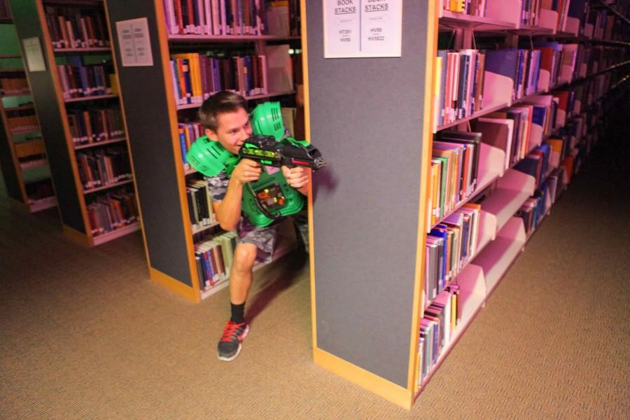 EWU student defends his territory between the book shelves during the laser tag event.