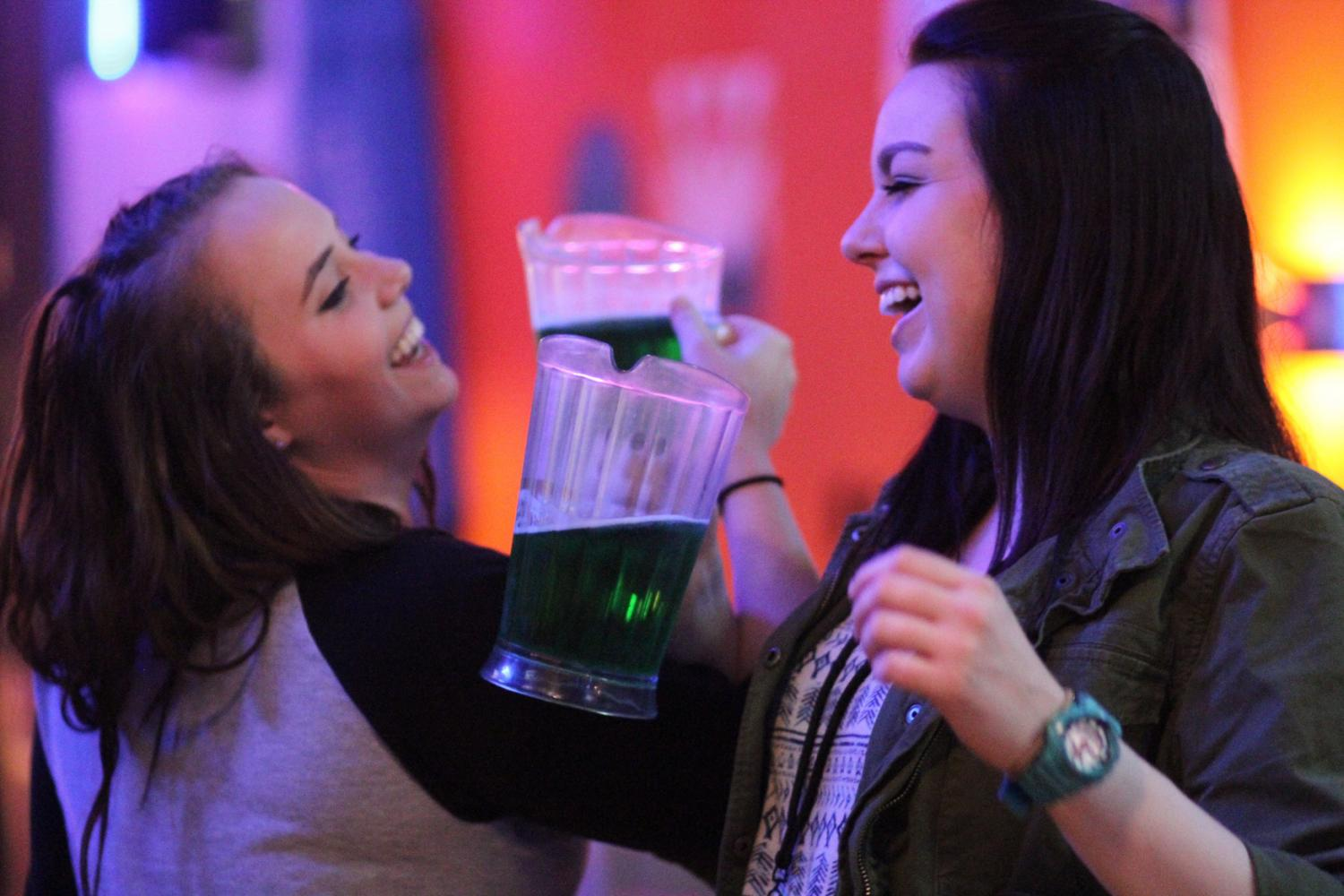 Two students crossing arms with pitchers of green beer at Monterey's Pub & Grub