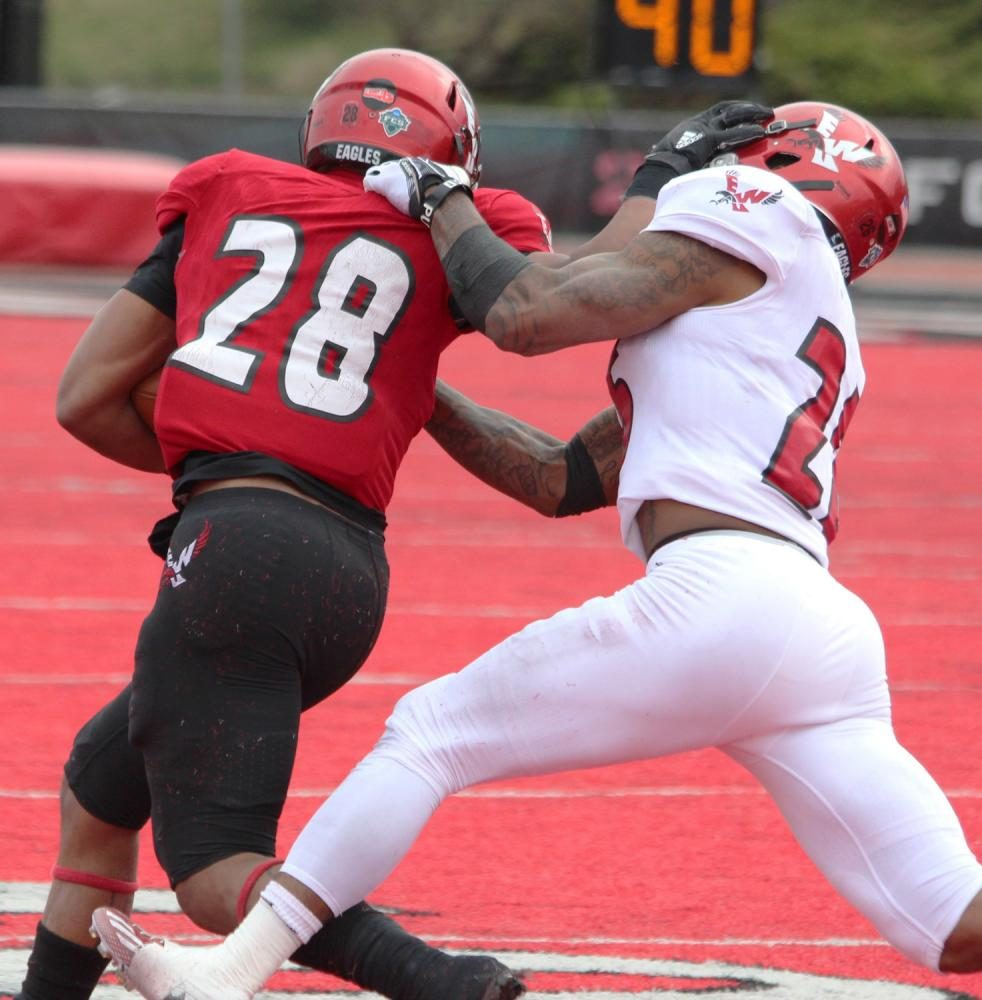 Running back Antoine Custer Jr. (28) stiff-arms defensive back Dehonta Hayes (26), at the Red-White spring game.
