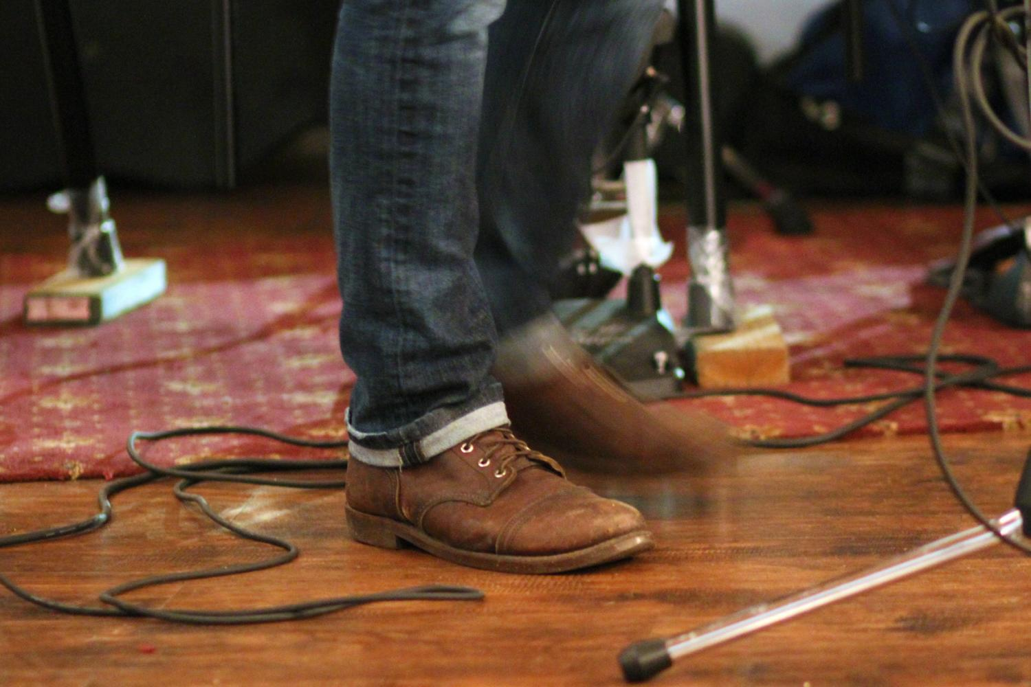 Micael Boucher stomping his feet while performing at The Mason Jar's open mic night