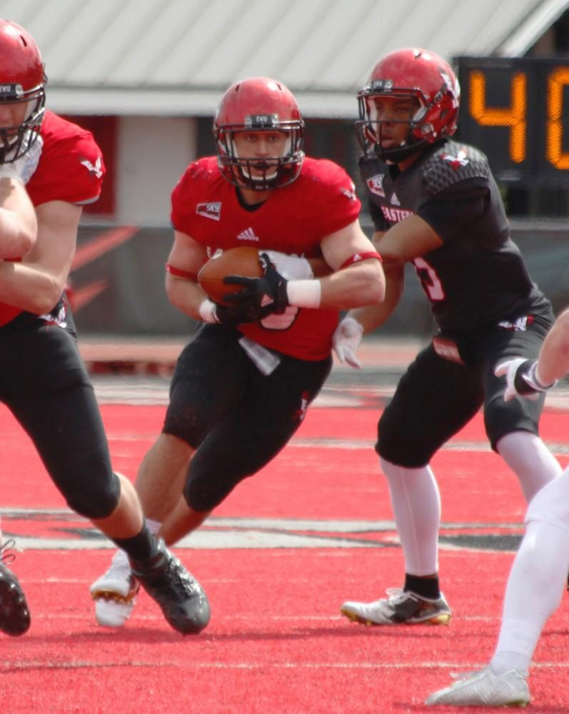 Quarterback Eric Barriere hands the ball off the running back Sam McPherson (20), at the Red-White spring game.