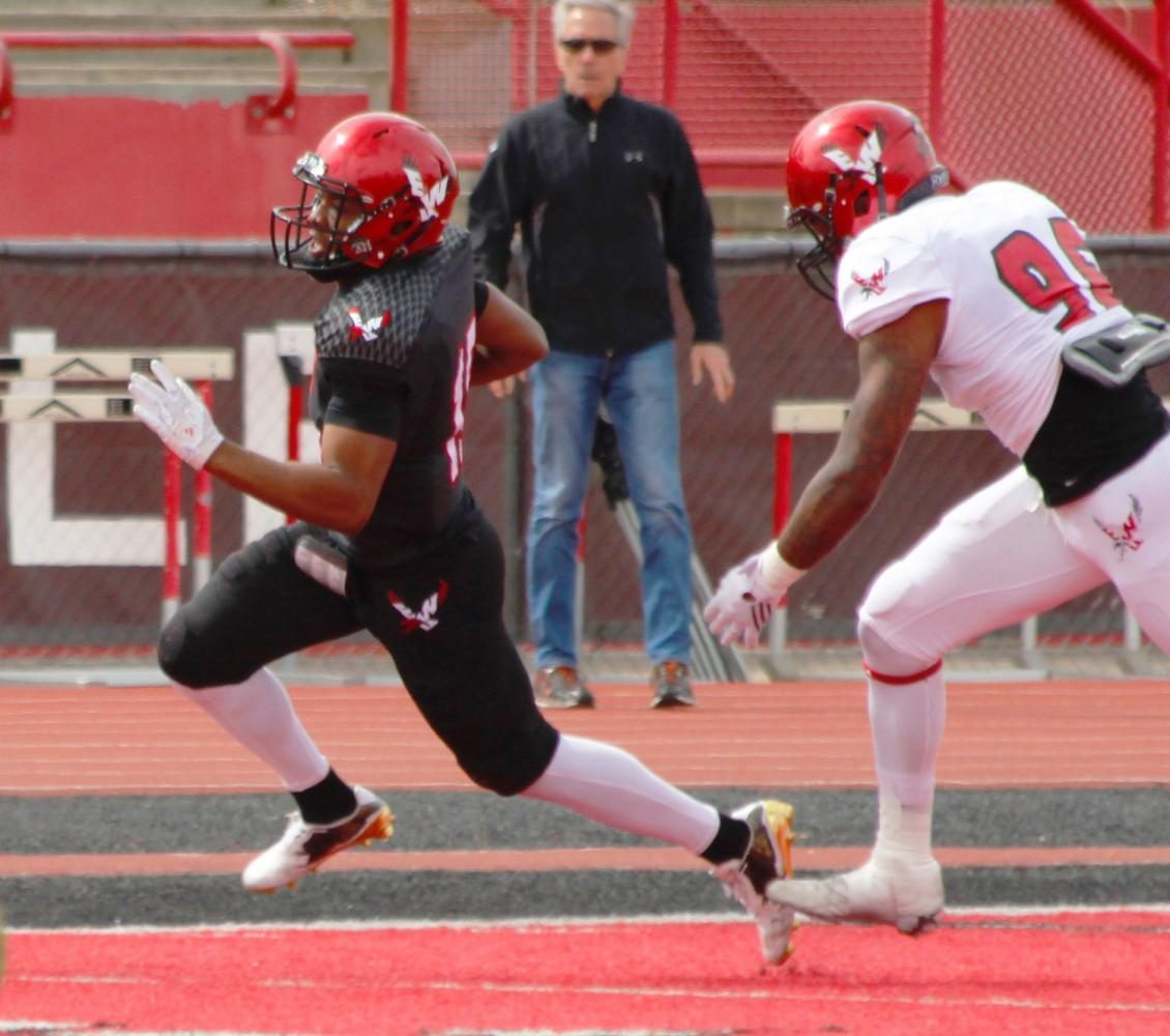 Quarterback Eric Barriere (15) scrambles around defensive lineman Darnell Hogan (96), at the Red-White spring game.