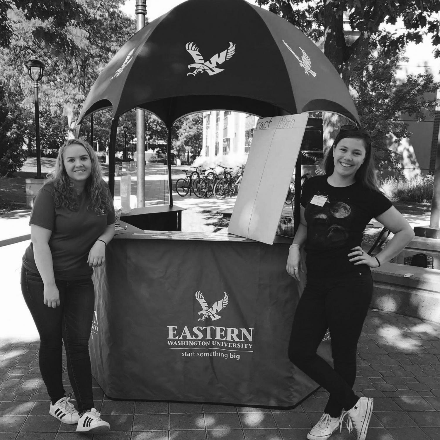 Sophomore Rylie Campbell (left) and Senior Carrie Cutler (right) stand with the Health Hut table at an event earlier this year. The wellness club gives students tips and swag at the hut twice a week | Photo courtesy of the EWU Health and Wellness Facebook page