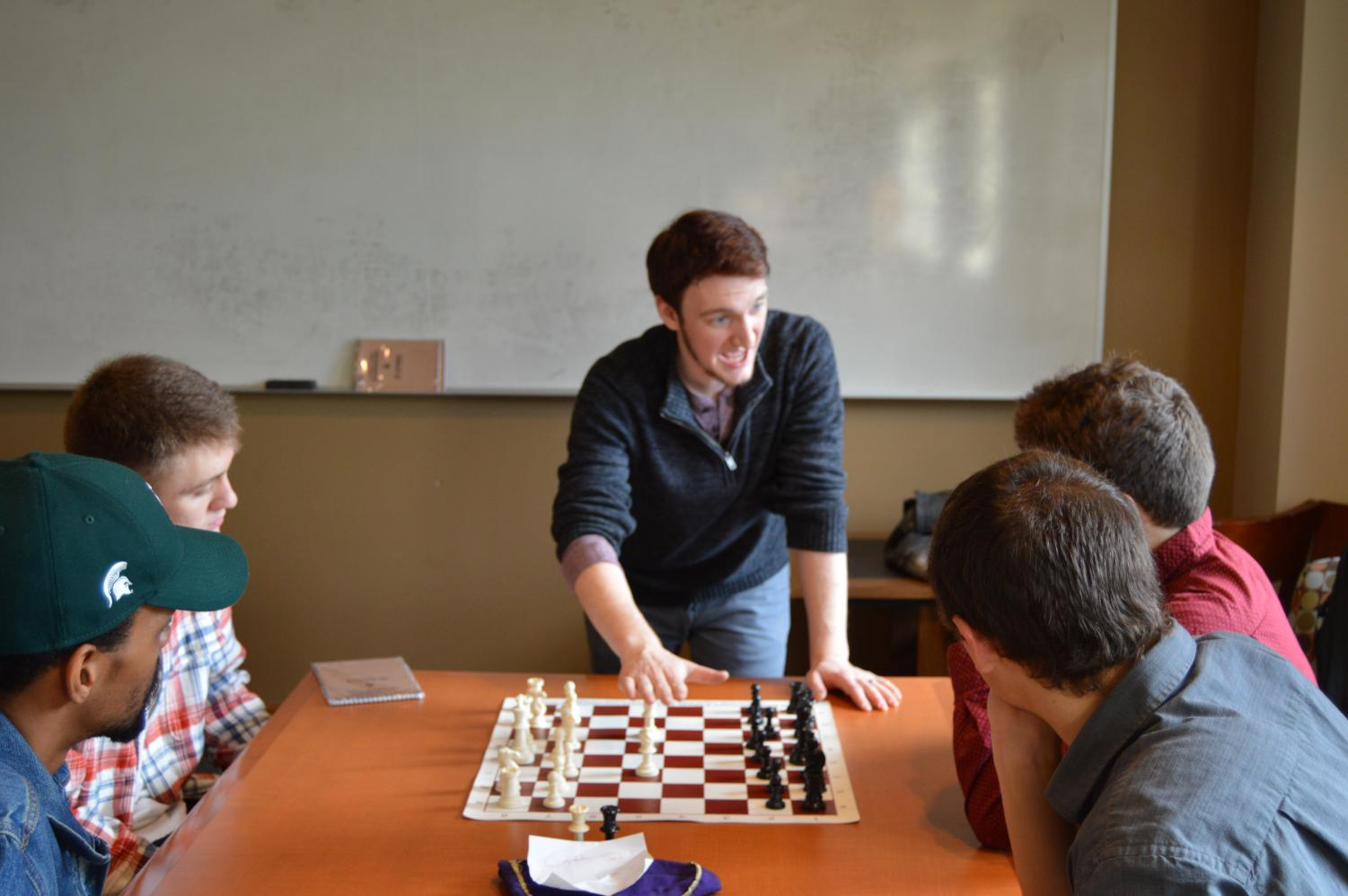Chess club president Raymond Shiner, a licensed chess coach, provides instruction to new players during a Friday meeting. The chess club has drop-in play on Fridays at noon   Jeremy Burnham for The Easterner