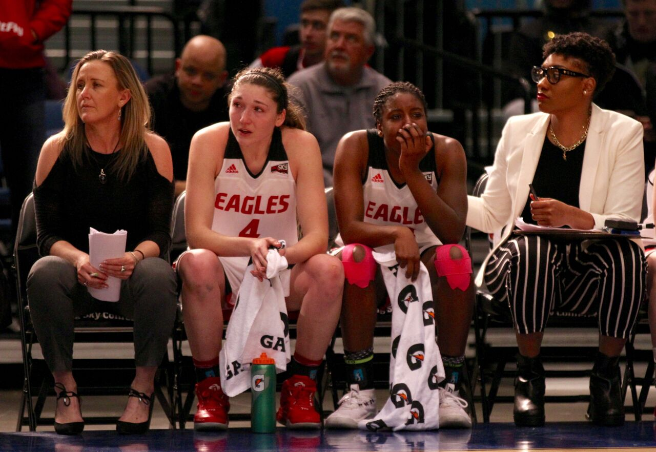 Seniors Delaney Hodgins (left) and Mariah Cunningham sit with assistant coaches during the waning moments of EWU's loss to Portland State. Hodgins scored 15 points against PSU | Brooks Nuanez, Skyline Sports
