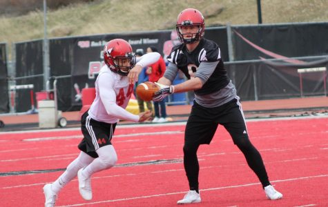 Senior quarterback Gage Gubrud hands the ball off to junior running back Dennis Merrit at EWU football's first spring practice on April 3. The Eagles are trying to improve on a 2017-18 season in which they went 7–4 overall, but missed out on the FCS playoffs. | Mckenzie Ford for The Easterner