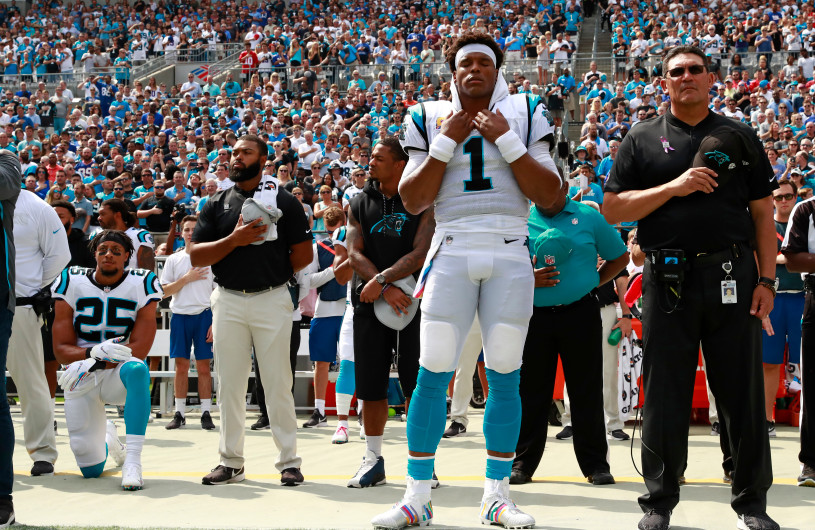 Carolina Panthers' safety Eric Reid (#25) kneels as quarterback Cam Newton (#1) and head coach Ron Rivera (far right) stand during the national anthem before last Sunday's game against the New York Giants | Photo courtesy of Jason E. Miczek, Associated Press