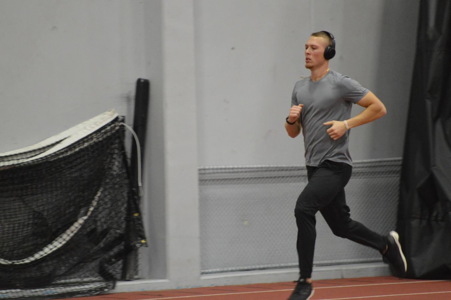 Senior hurdler Parker Bowden runs around the field house track on Jan. 10. Bowden Jr. finished second in the 60-meter hurdles at the Lauren McCuskey Memorial Open on Jan. 12.