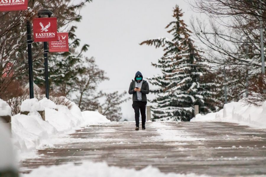 A man walks through EWU's campus during the second of two snow days. Eastern Washington has been facing above average snowfall this month in 2019.
