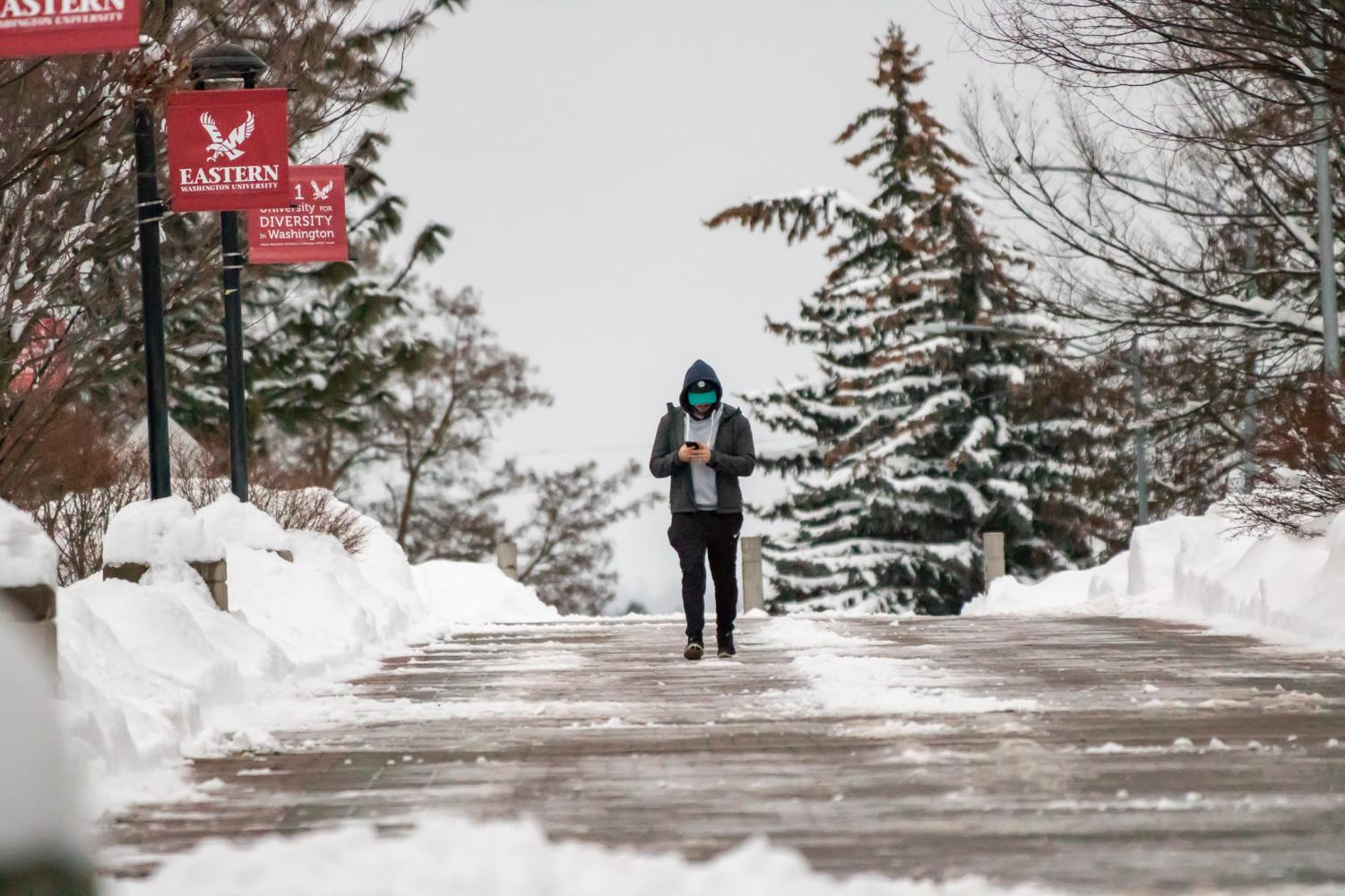 A man walks through EWU's campus during the second of two snow days. Eastern Washington has been facing above average snowfall this month.