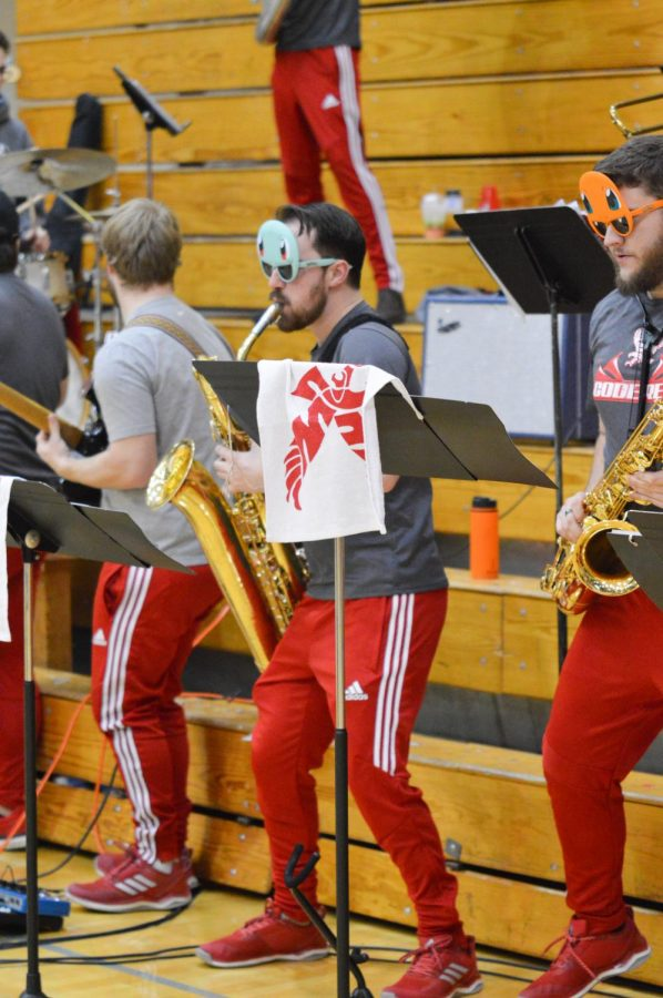 Senior+saxophone+player+Nicholas+Walsh+performs+with+Code+Red+at+a+basketball+game+on+Feb.+28.+During+games+band+members+typically+taunt+opposing+teams%2C+including+yelling+%2250%25+is+still+failing%22+every+time+a+player+makes+one-of-two+free+throw+attempts.+