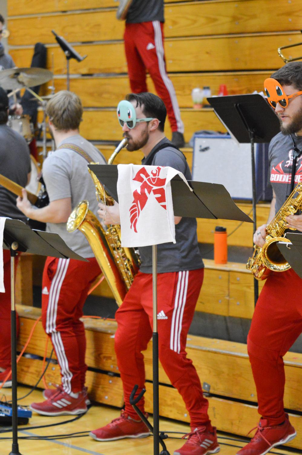 Senior saxophone player Nicholas Walsh performs with Code Red at a basketball game on Feb. 28. During games band members typically taunt opposing teams, including yelling