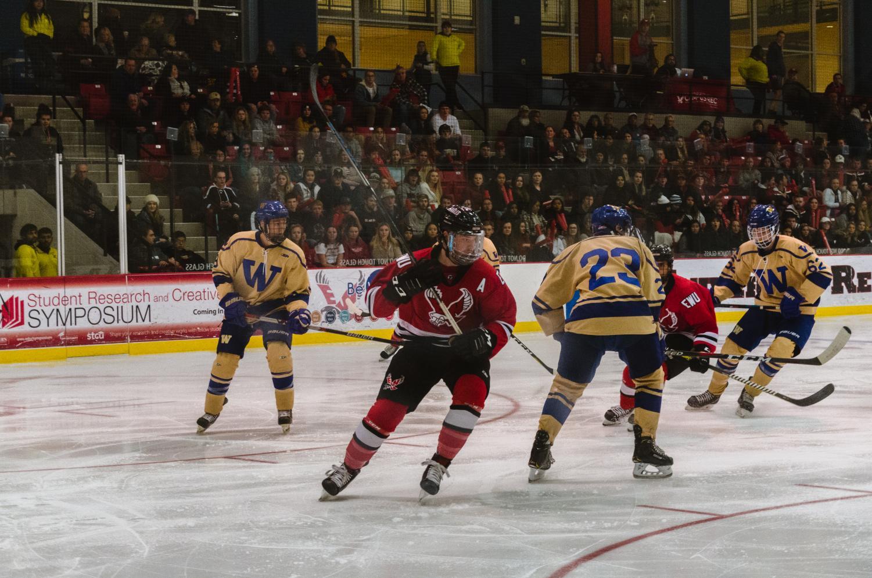 EWU sophomore forward Mitch Hunt (center) skates down the ice. Hunt had a hat trick in EWU's 9-3 victory over Washington Saturday.