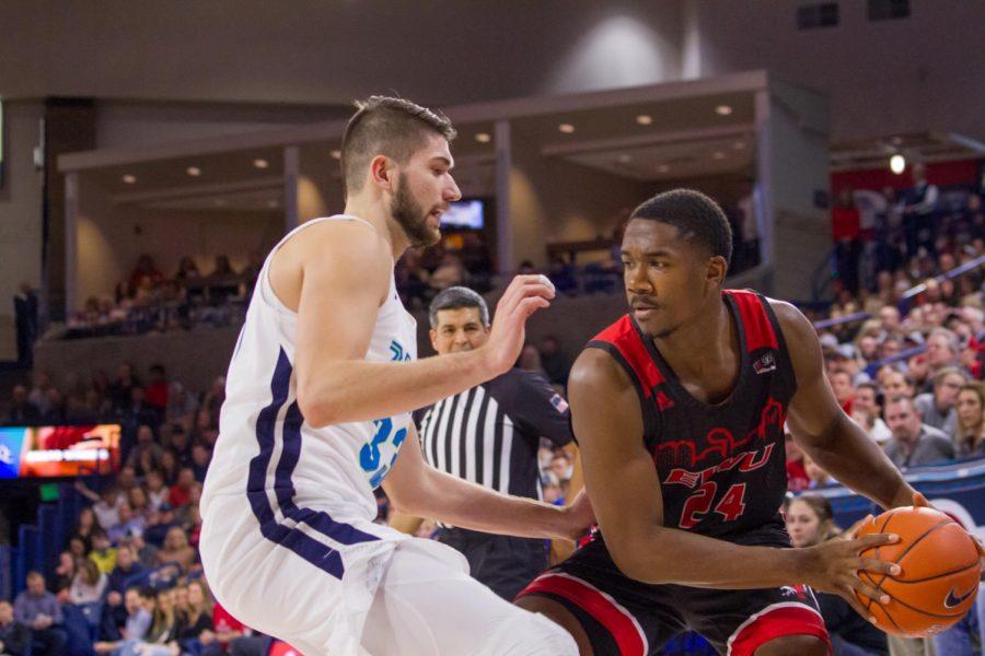 EWU sophomore guard/forward Kim Aiken Jr. looks to make a move against Gonzaga's Killian Tillie. Aiken scored 11 points in EWU's 112-77 loss Saturday.