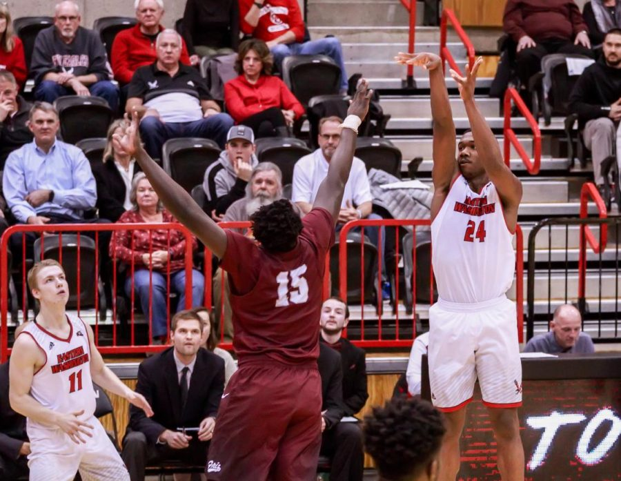 EWU sophomore guard/forward Kim Aiken Jr. shoots a jump shot over a Montana defender. UM returns to Reese Court Thursday for an important Big Sky Conference matchup.